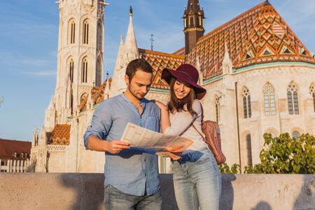 Young couple searching right direction on map from the point from Fisherman Bastion in Budapest with Matthias Church on background Banque d'images - 133254422