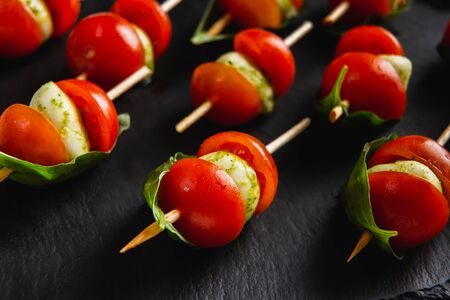Small snacks canape with cherry tomatoes, mozzarella on skewer on a black slate plate.