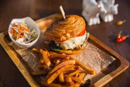 Delicious burgers with beef, tomato, cheese served with french fries and salad Banque d'images - 133314594