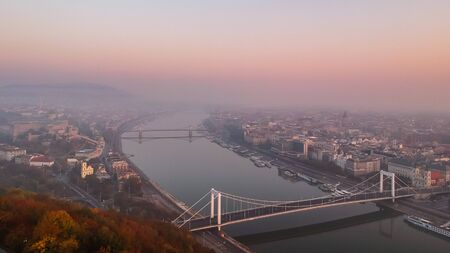 Aerial view to the Elisabeth Bridge and River Danube taken from Gellert Hill on sunrise in fog in Budapest, Hungary. Banque d'images - 133331342