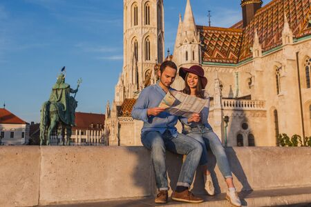 Young couple searching right direction on map from the point from Fisherman Bastion in Budapest with Matthias Church on background Archivio Fotografico