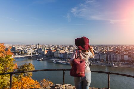 A happy young woman enjoying her trip to Budapest, Hungary from the point from Gellert Hill during sunrise in autumn