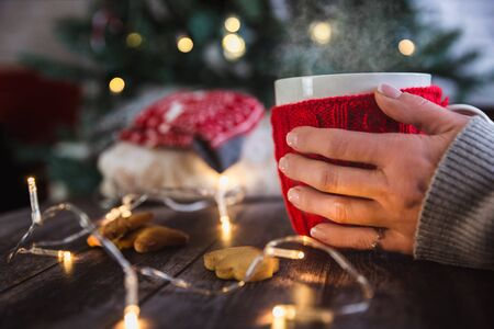 Woman hands holding Christmas coffee or tea red mug with steam, homemade gingerbread christmas cookies on a wooden table, sweeters on background