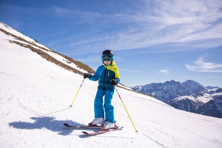 Little girl in blue and yellow ski costume skiing in downhill slope. Winter sport recreational activity