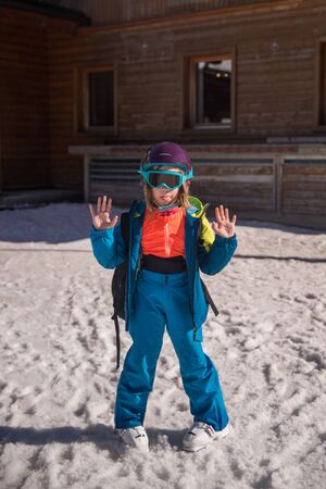 Portrait of cute happy skier girl in helmet and goggles in a winter ski resort is having a rest after skiing 版權商用圖片