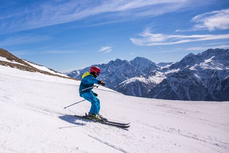 Little boy in blue and yellow ski costume skiing in downhill slope. Winter sport recreational activity