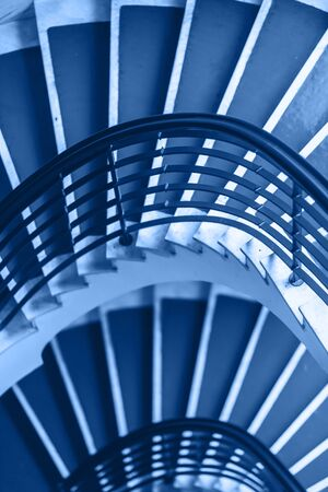 Classic Blue background made for Old blue spiral staircase inside an old house. Color of the Year 2020. 版權商用圖片