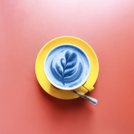 Flat lay of yellow hot trendy latte in blue color with art flower petals on the foam on coral table background. Color of the Year 2020.