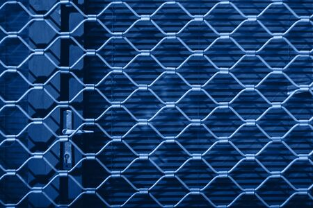 Iron texture of a steel grill on red shutters on the door. Blue background. 版權商用圖片