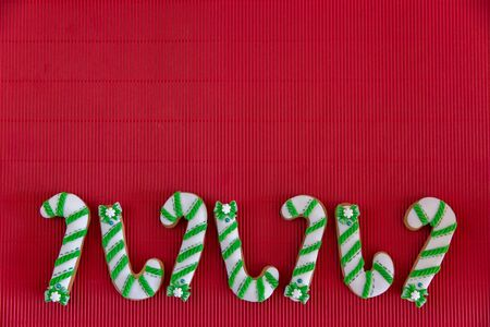 Hand painted Christmas gingerbread green and white candy cane and snowflakes on a beautiful red background. Card concept. Top view. Flat lay. Stock Photo