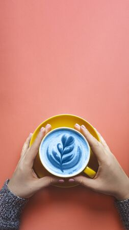 Yellow cup with latte in blue color with art flower petals on the foam on coral table background.