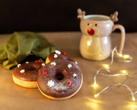 Christmas breakfast table with chocolate donuts decorated red and white sprinkles with hot cocoa in deer mug, Merry Christmas and Happy New Year