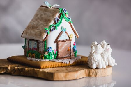 Homemade gingerbread house on wooden plate with two marzipan sheeps