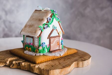 Homemade gingerbread house on wooden plate, close-up
