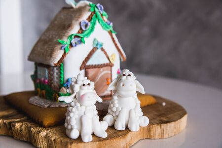 Homemade gingerbread house on wooden plate with two marzipan sheeps, close-up
