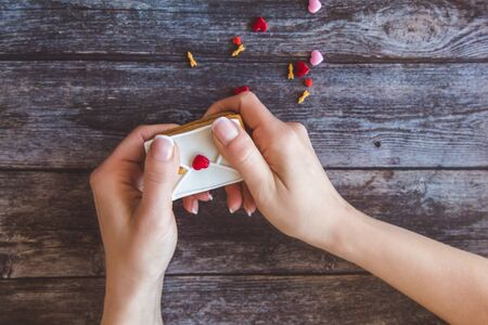 Baking Surprise Cookies with topping and icing on wooden background with pink heart. Woman holds a love letter