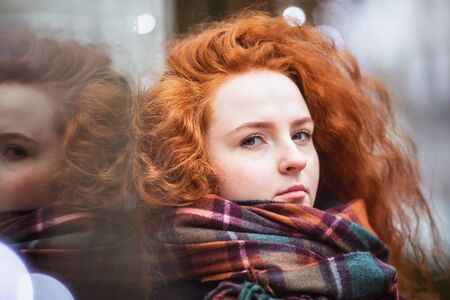 Portrait red hair girl in modern colorful scarf outside