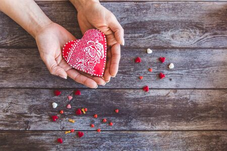Valentine day gingerbread cookies heart in wooman hands with sprinkles on wooden background
