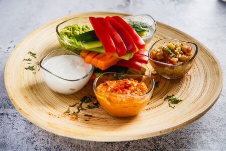 Plate with assorted raw vegetables - carrot, bell pepper, cucumber with various dips