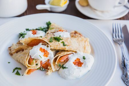 White plate with pancakes with salmon and red caviar, served with sour cream for breakfast