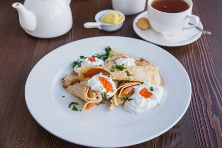 White plate with pancakes with salmon and red caviar, served with sour cream for breakfast, menu restaurant 版權商用圖片