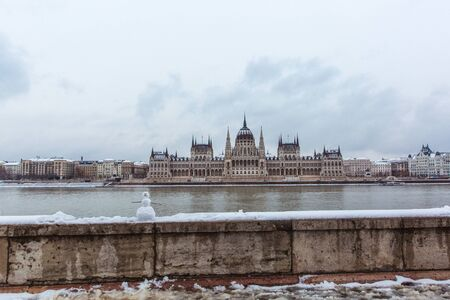 Hungarian parliament building at winter with snow. Snowman on the river bank, Budapest, Hungary