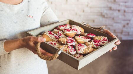 Young womans hands hold big box with hommade cookies hearts. Present for Valentines day, close-up 版權商用圖片