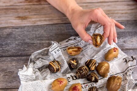 Womans hand holding homemade vegetarian chocolate energy balls . Healthy sweets made from nuts and figs. Handmade natural vegetarian dessert concept. Copy space