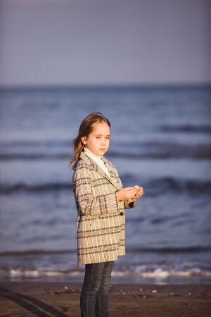 Portrait of little fashionable girl walking near sea