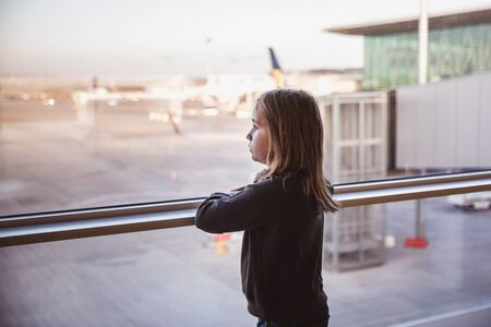 Little girls is looking to airplans in airport waiting lounge in Budapest