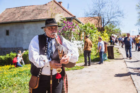 HOLLOKO, HUNGARY - April 12, 2019: Easter festival in the folklore village of Holloko in Hungary. A villager plays a national musical instrument