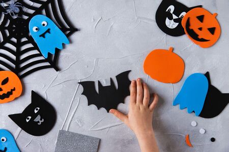 How to make decore for Halloween greetings and fun. Children art project. DIY concept. Kids hands makes paper craf. Step by step photo instruction. Bat blank from paper