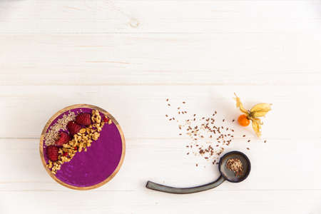 Acai smoothie, granola, seeds, fresh berries in a wooden bowl. Plate filled with berries and ceramic spoon on white wooden background. Overhead, top view, flat lay, copy space
