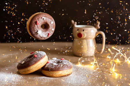 Christmas breakfast table with flying chocolate donut decorated with red and white sprinkles, hot cocoa in deer mug on background Imagens