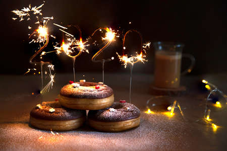 Donuts with christmas decoration with an igniting 2020 Shaped Sparkler. Imagens