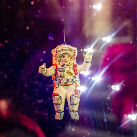 Christmas toy cosmonaut on the Christmas tree in neon light