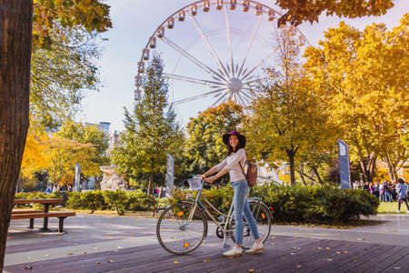 A happy young woman travel by bicycle and stop near the Budapest Eye big Ferris wheel in Budapest