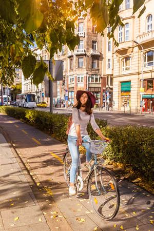 A happy young woman is traveling by bicycle on the streets in Budapest in sunny day