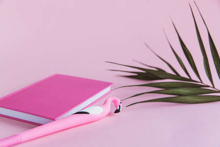 Pink notebook for notes, funny flamingo pen and green palm leaves on pink pastel background 免版税图像