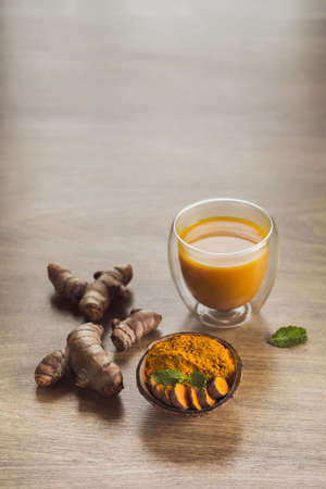 Organic orange turmeric drink, tea with cinnamon in a glass mug with fresh turmeric powder on wooden background. Indian oriental low cholesterol spices. Food and drink, diet nutrition