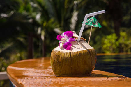 Fresh cold coconut with cocktail straw near the pool