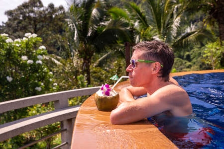Handsome man relaxes by the outdoor pool and drinks a coconut with palm trees in the background. Summer concept.