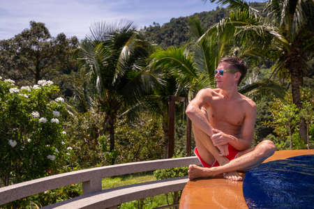 Handsome young man with a naked torso relaxes by the outdoor pool with palms on background. Healthy lifestyle concept. Banco de Imagens