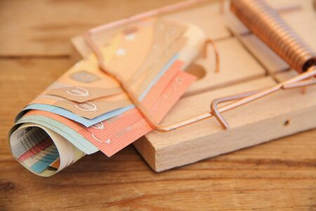 A wooden mousetrap with banknotes 版權商用圖片