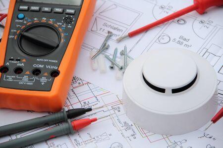 Detector de humo con un destornillador y un dispositivo de medición en un diagrama de circuito Foto de archivo