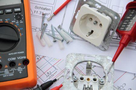 Zócalos con un destornillador y un dispositivo de medición en un diagrama de circuito Foto de archivo