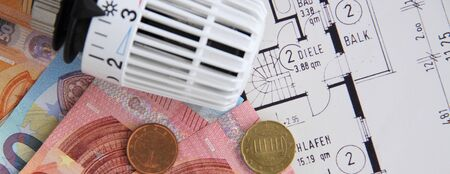 A heating thermostat with money on a blueprint