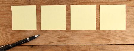 Four yellow notes on a wooden table