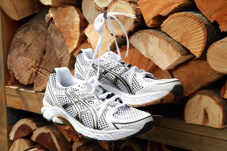 A pair of jogging shoes hang on a firewood rack of firewood