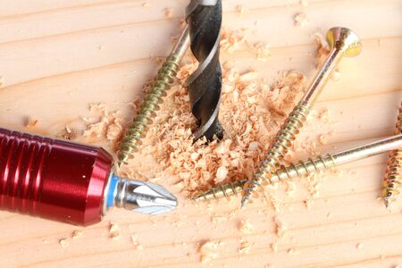 Drill and screw on a wooden board